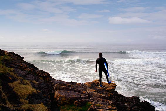 A surfer looks at waves at Tullan Strand, County Donegal, Ireland