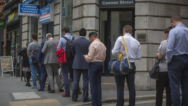 People queue to exchange money on Cannon Street, London ahead of the EU referendum vote tomorrow.