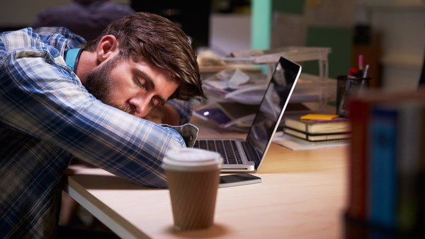 Male Office Worker Asleep At Desk Working Late On Laptop.