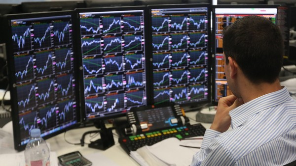A trader monitors financial information on computer screens on the trading floor at Panmure Gordon & Co., as results continue to be announced in the 2015 general election in London, U.K., on Friday, May 8, 2015. David Cameron is on course to remain prime minister at the head of a minority government after the U.K. general election, an exit poll and early results indicated. The pound jumped. Photographer: Chris Ratcliffe/Bloomberg