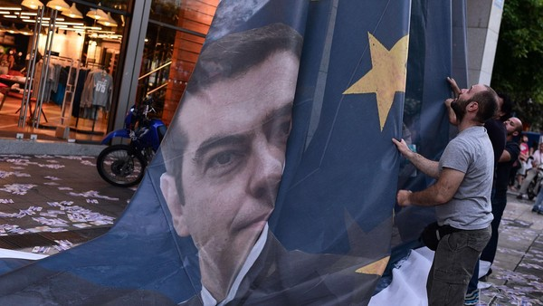 "TOPSHOTS Protesters take down a huge banner bearing a picture of Greek Prime Minister Alexis Tsipras on a European Union flag from the ministry of finance in Athens as they end the occupation of the building on June 11, 2015. The Greek government on Thursday said it would ""intensify"" efforts to resolve differences with its EU-IMF creditors to reach a deal that would give the country desperately needed bailout funds. AFP PHOTO / LOUISA GOULIAMAKILOUISA GOULIAMAKI/AFP/Getty Images"