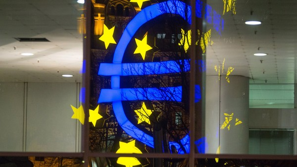 The euro sign sculpture is reflected in office windows as it stands outside the former European Central Bank (ECB) headquarters, at night in Frankfurt, Germany