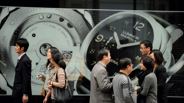 Pedestrians walk past a luxury watch shop in Shanghai on March 29, 2012