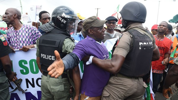 "TOPSHOT - Anti riot policemen face a disgruntled faction of workers and civil society groups marching with a banner and placards during a protest demanding that the government reinstate prices of fuel at 86.50 naira ($0.43, 0.38 euros) per litre in Lagos, on May 18, 2016. Nigeria's government on May 18 warned against ""illegal strike action"" after some union members vowed to press ahead with a national strike over petrol price rises despite a court injunction. / AFP / PIUS UTOMI EKPEI (Photo credit should read PIUS UTOMI EKPEI/AFP/Getty Images)"
