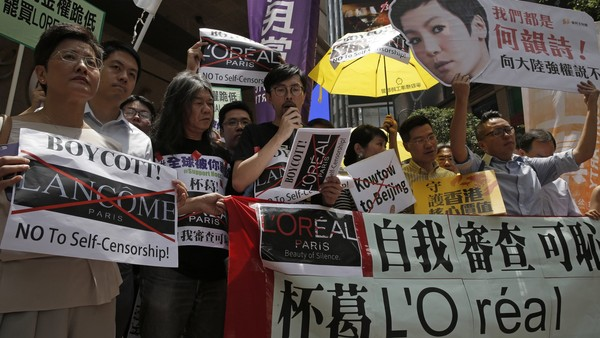 "Protestors display placards with the picture of local singer Denise Ho outside a department store in Hong Kong's Times Square, Wednesday, June 8, 2016. French cosmetics company Lancome has sparked a backlash in Hong Kong after it canceled a promotional concert featuring a singer Ho known for her pro-democracy views, with many accusing it of caving to political pressure from Beijing. The banner reads ""Boycott L'Oreal! No Self- censorship"". (AP Photo/Kin Cheung)"