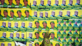 A woman walks past posters for ruling party Chama Cha Mapinduzi (CCM) presidential candidate John Magufuli and parliamentary candidate Hassan Zungu on October 20, 2015 in Dar es Salaam