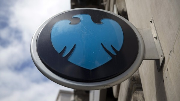 A Barclays logo sits on a sign outside a Barclays Plc bank branch in London, U.K., on Wednesday, May 7, 2014. Barclays will cut 7,000 jobs at its investment bank, bringing the total number of jobs to be cut across the firm by 2016 to 19,000, including the 12,000 the lender announced in February it would cut this year, Barclays said in a statement. Photographer: Simon Dawson/Bloomberg