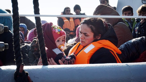 TOPSHOT - A mother holds her child as she arrives along with other migrants and refugees aboard a Greek coast guard boat to the port of Mytilene on the Greek island of Lesbos on March 29, 2016, after being rescued by Frontext and Greek coast guards. The United States will provide an additional $20 million (18 million euros) in aid for refugees in Europe, a senior US official said on March 28, 2016. Most of the funds -- $17.5 million -- will be given to the UN refugee agency, Higginbottom said during a visit to Lesbos, the island that has experienced most of the refugee arrivals registered in Greece since 2015, where there are over 2000 refugees and migrants according to the Greek government. / AFP PHOTO / --/AFP/Getty Images