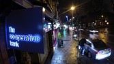 "An illuminated logo sits on a sign outside a Co-Operative Bank Plc branch, a unit of Co-Operative Group Ltd., at night in Manchester, U.K., on Sunday, Dec. 14, 2014. Co-Op Bank Chief Executive Officer Niall Booker earlier this month said it ""would come as no surprise"" if the bank didn't meet the Bank of England's minimum capital requirements when the results of the stress test are released on Dec. 16, which models how banks would fare in another financial crisis. Photographer: Paul Thomas/Bloomberg"