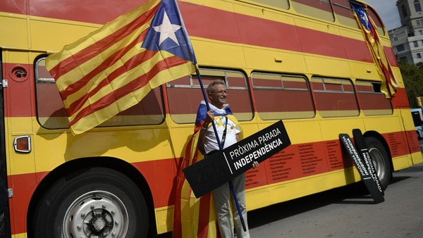 "A man poses with a sign reading ""Next stop: Independence"" and an ""Estelada"" (pro independence Catalan flag) past a bus with the colours of the Catalan flag"