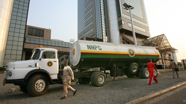 Men walk past a Nigerian National Petroleum Corporation tanker outside the NNPC headquarters in Abuja, Nigeria