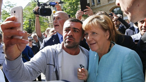"File photo of a migrant taking a selfie with German Chancellor Angela Merkel outside a refugee camp near the Federal Office for Migration and Refugees in Berlin, Germany, September 10, 2015. Time magazine named German Chancellor Angela Merkel its 2015 ""Person of the Year"" on December 9, 2015, noting her resilience and leadership when faced with the Syrian refugee crisis and turmoil in the European Union over its currency this year. REUTERS/Fabrizio Bensch/Files"