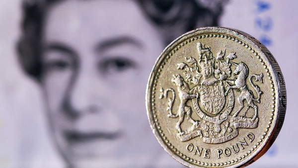 A one pound sterling coin sits in front of a British five pound banknote in this arranged photograph in London, U.K., on Tuesday, Feb. 9, 2016. The pound has been falling versus the dollar since the middle of 2015 and accelerated its slide this year, reaching an almost seven-year low of $1.4080 on Jan. 21. Photographer: Chris Ratcliffe/Bloomberg
