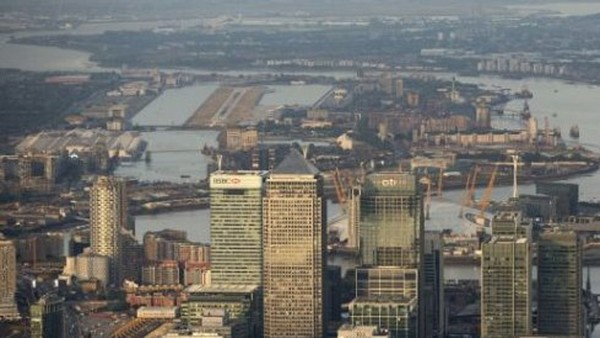Aerial Views Of Canary Wharf And The City...Skyscrapers in the Canary Wharf business, financial and shopping district, including HSBC Holdings Plc, center left, One Canada Square, center, and Citigroup Inc., are seen in this aerial photograph, as London City airport, far left, and the Thames Barrier, far right, are seen in the background in London, U.K., on Tuesday, June 16, 2015. Britain had its smallest budget deficit for any May since 2007 as tax income jumped, handing a boost to Chancellor of the Exchequer George Osborne as he prepares to unveil the first budget of the new Conservative-only government. Photographer: Matthew Lloyd/Bloomberg