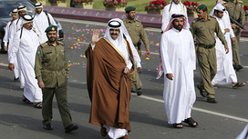 Qatari Emir Sheikh Hamad bin Khalifa al-Thani waves as he arrives to attend National Day celebrations in Doha...Qatari Emir Sheikh Hamad bin Khalifa al-Thani (front C) waves next to members of a security team as he arrives to attend National Day celebrations in Doha