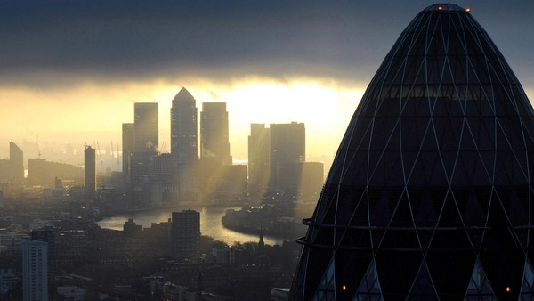 EMBARGOED TO 0001 MONDAY JANUARY 25 File photo dated 25/02/10 of the 'Gherkin' and Canary Wharf at sunrise in the City of London.
