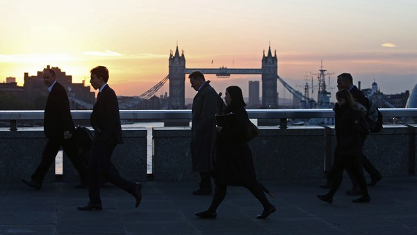 Pedestrians walk across London Bridge towards the City of London financial district, as Tower Bridge spans the River Thames in London, U.K., on Friday, Oct. 10, 2014. Vacancies in the City rose to 7,905 in September from 7,371 in the year-earlier period, London-based recruitment firm Morgan McKinley said in a statement today. Photographer: Chris Ratcliffe/Bloomberg