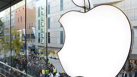 Customers queue to enter the Apple Store where a giant logo is displayed