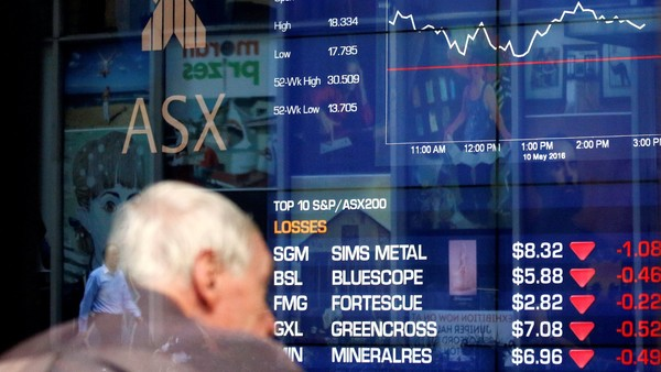An investor sits in front of a board displaying stock prices at the Australian Securities Exchange (ASX) in Sydney, Australia, May 10, 2016. REUTERS/Steven Saphore FOR EDITORIAL USE ONLY. NO RESALES. NO ARCHIVES