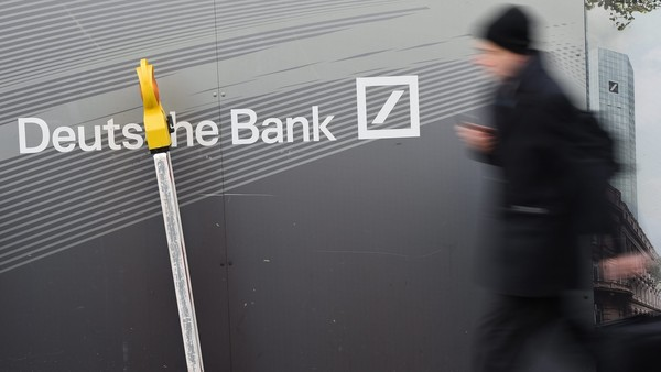 epa05115538 A man walks past a construction site fence written with 'Deutsche Bank' in Frankfurt am Main, Germany, 21 January 2016. Deutsche Bank, Germany's largest lender, will likely report a net loss of about 6.7 billion euros (7.3 billion dollars) for 2015, largely due to restructuring charges and money set aside to cover legal costs. Full-year revenue for 2015 will likely be around 33.5 billion euros, the bank said in a statement 20 January 2016. EPA/ARNE DEDERT