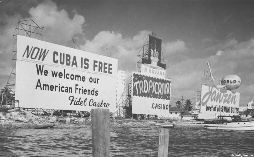 An advertisement on the Miami waterfront welcomes Americans to Cuba, but US - Cuba relations had already deteriorated after Cuba confiscated land from US citizens. By November, Cuba had also taken over virtually all US assets including sugar mills, oil refiners, railways, and hotels and the US had declared a full economic embargo on the island.