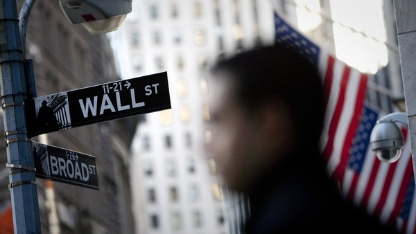 A pedestrian walks past the Wall Street street sign in front of the New York Stock Exchange (NYSE) in New York, U.S., on Tuesday, Feb. 28, 2011. U.S. stocks were little changed, after the Standard & Poor's 500 Index rose to an almost four year high, as a better-than-estimated consumer confidence report offset disappointing home and durable goods orders data. Photographer: Scott Eells/Bloomberg