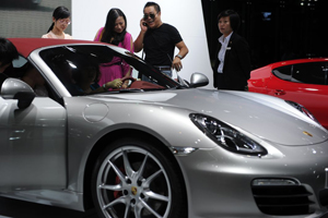 Visitors look at a Porsche Boxster car
