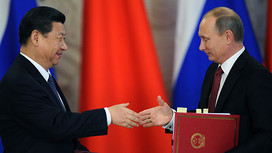 Russia's President Vladimir Putin (R) shakes hands with his Chinese counterpart Xi Jinping