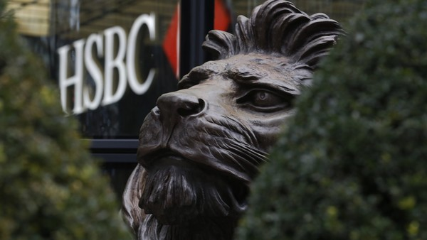 A sculpture of a lion, seen through hedges, sits outside the main entrance to the HSBC Holdings Plc headquarters in the Canary Wharf business, financial and shopping district in London, U.K., on Saturday, Feb. 13, 2016. HSBC's board will meet on Sunday to decide whether to shift its headquarters from London, according to two people with knowledge of the decision. Photographer: Luke MacGregor/Bloomberg