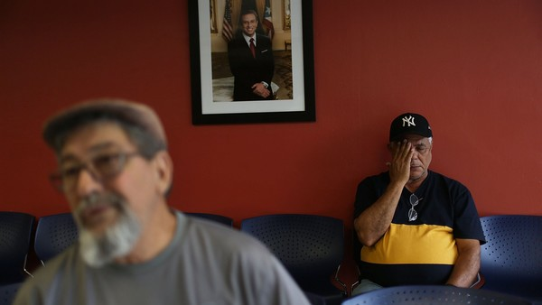SAN JUAN, PUERTO RICO - JUNE 30: Sitting near a portrait of Puerto Rican Governor Alejandro Garcia Padilla, Juan Menendez Perez and Francisco Almonte, (L-R) who are without jobs, wait to search for available work at an unemployment office a day after the governor gave a televised speech regarding the governments $72 billion debt on June 30, 2015 in San Juan, Puerto Rico. The Governor said in his speech that the people will have to sacrifice and share in the responsibilities for pulling the island out of debt. (Photo by Joe Raedle/Getty Images)