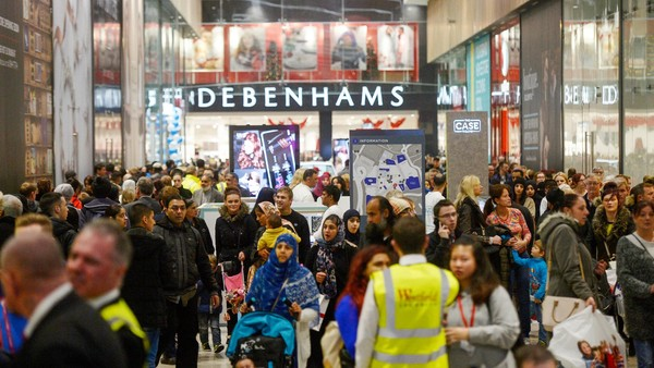 Shoppers pass in front of the Debenhams Plc department store at The Broadway shopping complex in Bradford, U.K. on Thursday, Nov. 5, 2015. The $419 million, 550,000 square-foot complex is managed by Westfield Corp. and owned by a group of investors led by property fund manager Meyer Bergman Ltd. Photographer: Matthew Lloyd/Bloomberg