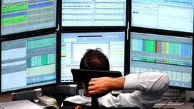 A financial trader monitors his computer screens.