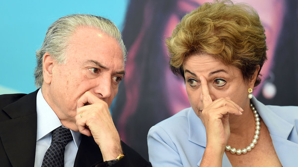 Brazilian President Dilma Rousseff (R) and Vice-President Michel Temer attend the launching ceremony of the Investment Program in Energy at Planalto Palace in Brasilia, on August 11, 2015. Analysts say Brazil's once booming economy suffers deep underlying illnesses, notably the massive corruption scandal unfolding at national oil company Petrobras and rippling across other top companies and into political circles. It is also on the brink of recession. According to a recent poll that put Rousseff's approval rating at eight percent, she is now Brazil's most unpopular democratically elected president since a military dictatorship ended in 1985. AFP PHOTO / EVARISTO SA (Photo credit should read EVARISTO SA/AFP/Getty Images)