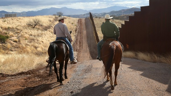 A US border patrol officer liaises with a local rancher at Nogales, Arizona