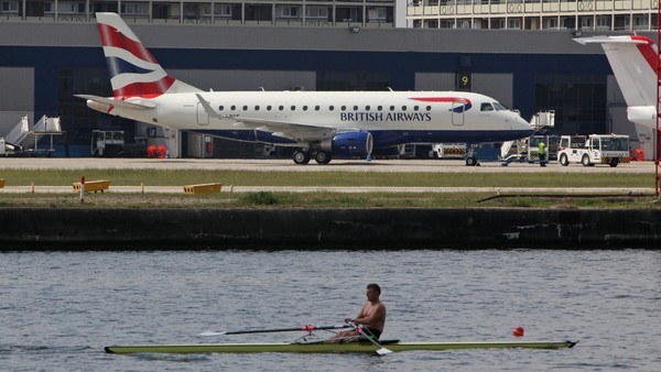 A rower passes a British Airways airplane as it sits on the tarmac at City Airport in London, U.K., on Friday, May 21, 2010. British Airways Plc said it will break even this year, rebounding from a record loss, if demand for business trips continues to gain and Chief Executive Officer Willie Walsh wins his 15-month tussle over cabin-crew expenses. Photographer: Chris Ratcliffe/Bloomberg