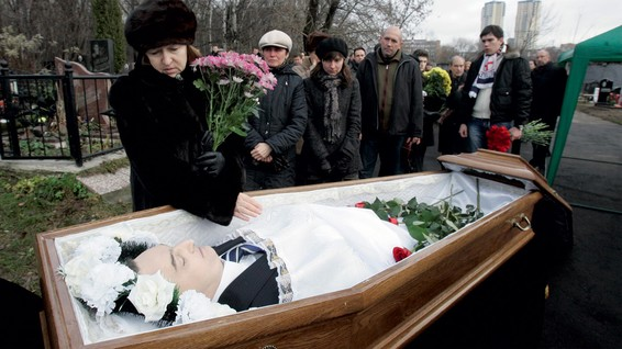 Nataliya Magnitskaya (left) grieves over the body of her son, Sergei Magnitsky, at his funeral at a Moscow cemetery on November 20 2009