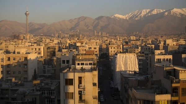 The snow capped peaks of the Alborz mountain range stand beyond buildings and rooftops on the city skyline in Tehran, Iran, on Wednesday, Nov. 25, 2015. Iran will encourage foreign partners and investment as sanctions are lifted and the country seeks to boost its economy after July's nuclear agreement with the world powers, President Hassan Rouhani said. Photographer: Simon Dawson/Bloomberg