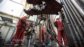 Oil workers use a drilling machine